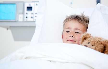 Sick cute little boy lying in a hospital bed  photo