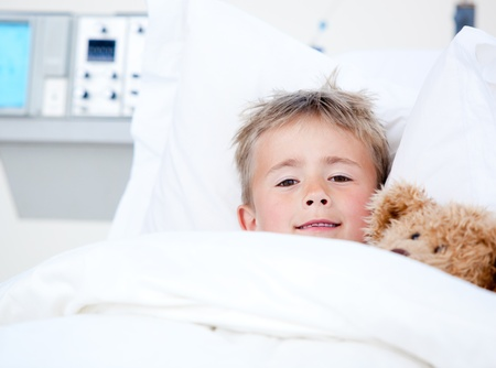 Sick adorable little boy lying in a hospital bed with his teddy bear photo