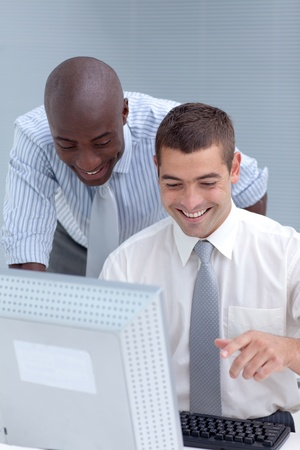 Caucasian and Afro-American businessmen using a laptop  photo