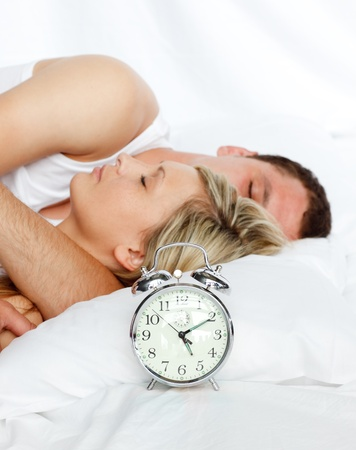 Couple in bed with focus in alarm clock photo