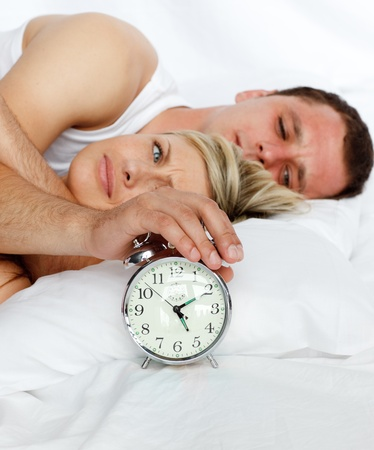 Couple in bed with alarm clock going off photo