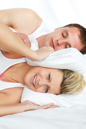 snore: Woman trying to sleep with man snoring Stock Photo