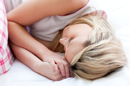 Blond young woman sleeping on a bed  photo