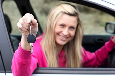 Smiling driver showing a key after bying a new car  photo