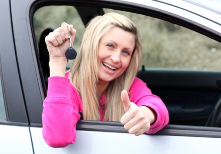 Happy female driver showing a key after bying a new car  photo