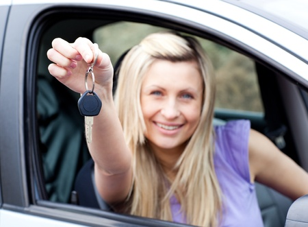 Enthusiastic young driver holding a key after bying a new car