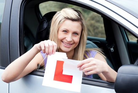 driving school: Cheerful young female driver tearing up her L sign  Stock Photo
