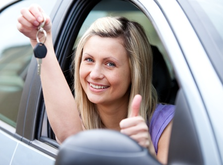 l plate: Lively female driver showing a key after bying a new car