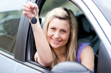 Attractive young driver holding a key after bying a new car  photo