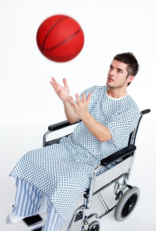 Patient in wheelchair playing with a basket ball photo