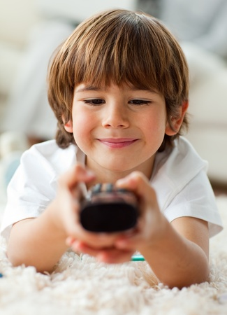 Cute little boy holding a remote lying on the floor  photo