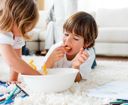 Cute children eating chips and drawing  photo