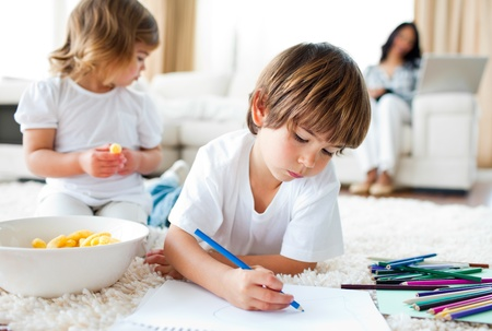 Happy children eating chips and drawing photo