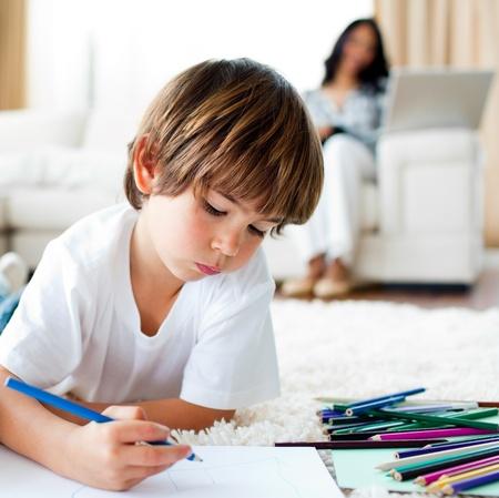 Koncentrerad liten pojke ritning och hans syster äta chips Stockfoto