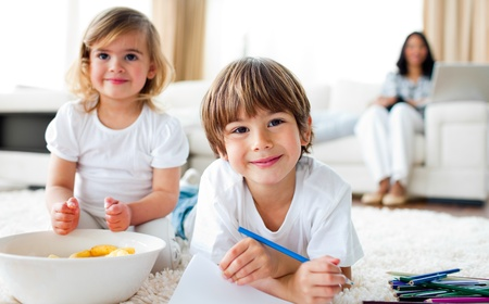 Smiling siblings eating chips and drawing  photo
