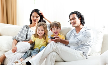 Excited little boy watching TV with his family Stock Photo - 10095158