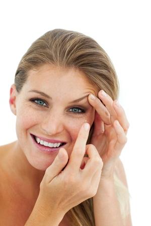 eye wear: Mujer, sonriente, poniendo una lente de contacto Foto de archivo