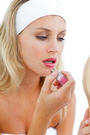 Concentrated woman applying lipstick  photo