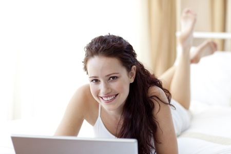 Smiling woman using a laptop in bed photo
