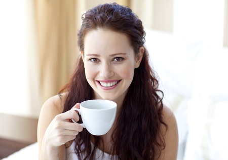 woman drinking coffee: Smiling woman drinking a cup of coffee in bedroom