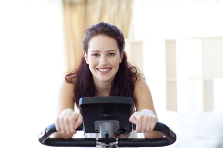 static bike: Smiling woman doing spinning at home Stock Photo