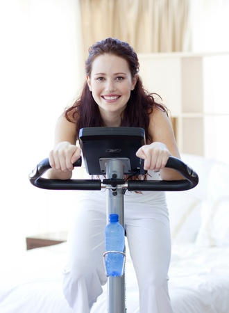 static bike: Woman doing spinning bike at home