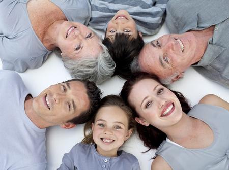 Lycklig familj liggande på golvet med huvuden ihop