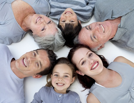 lying on floor: High angle of family lying on floor with heads together
