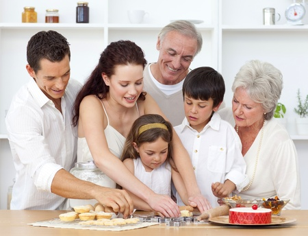 Parents, grandparents and children baking in the kitchen photo