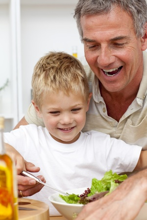 Happy grandfather eating a salad with grandson photo