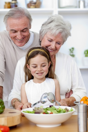 Happy grandparents eating a salad with granddaughter photo