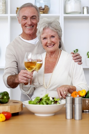 Happy senior couple eating a salad in the kitchen photo
