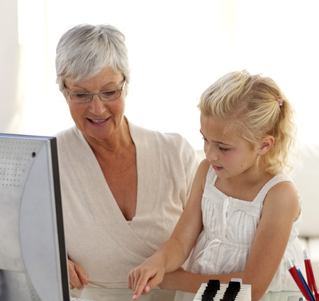 Little girl explaining her grandmother how to use a computer photo