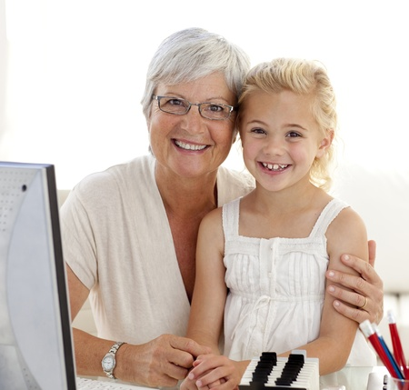 granddaughters: Portrait of granddaughter and grandmother using a computer Stock Photo