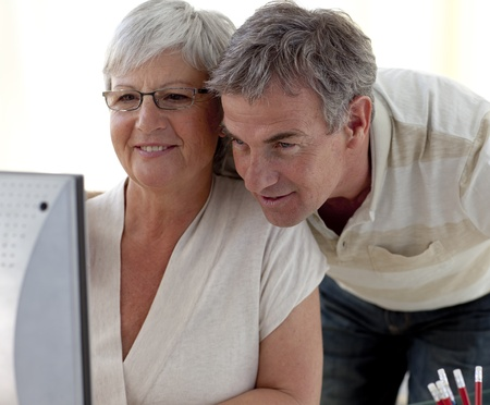 Portrait of senior couple using a computer at home photo