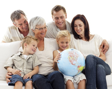 terrestrial: Big family on sofa looking at a terrestrial globe Stock Photo