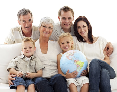 family on couch: Big family on sofa holding a terrestrial globe