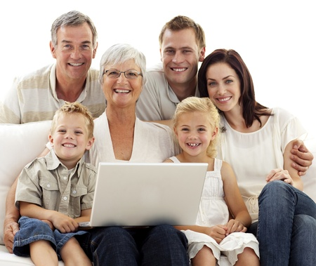 Smiling family using a laptop at home photo