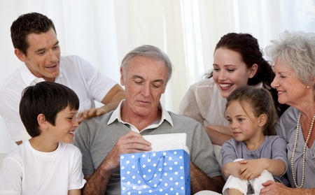Family giving to grandfather a present photo