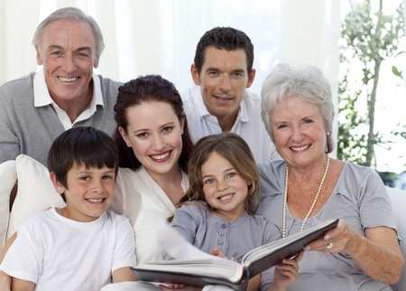 grandfather and grandmother: Smiling family looking at a photograph album Stock Photo