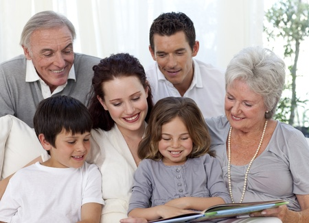 Family sitting on sofa reading a book photo