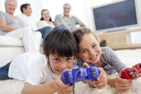 niños jugando videojuegos: Niños jugando videojuegos en suelo y familia en sofá