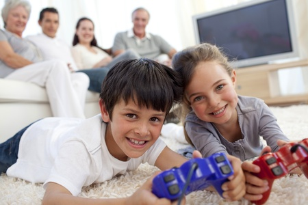 Children playing video games and family on sofa photo