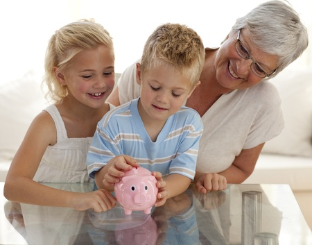 Grandmother and children saving money in a piggybank photo