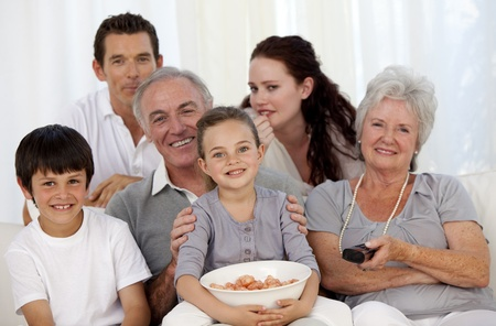 Family eating chips and watching television photo
