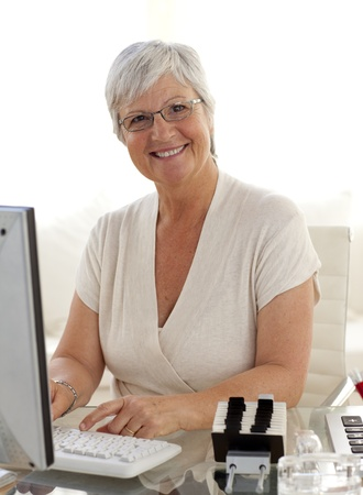 Smiling senior woman working with a computer photo