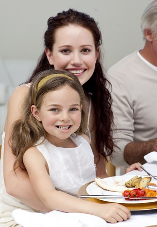 Mother and daughter having dinner with their family photo