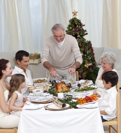 Family celebrating Christmas dinner with turkey at home photo