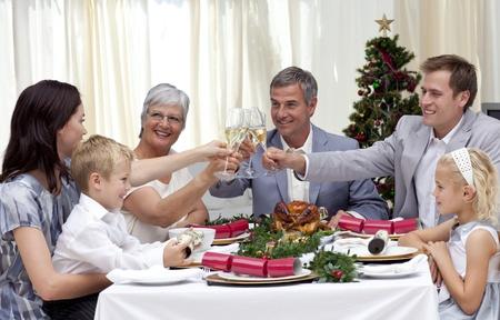 Familie drinken van een toast op een kerstdiner Stockfoto