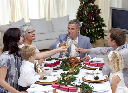 Family tusting in a Christmas dinner with champagne photo